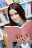 Young female student browses the book Royalty Free Stock Photos