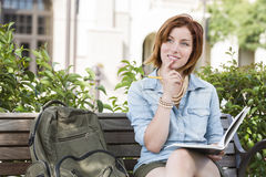 Young Female Student On Campus with Backpack on Bench Stock Image