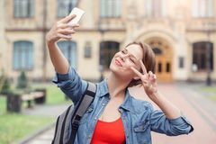 Young student with backpack at university campus standing taking selfie on smartphone showing v sign looking camera stock image