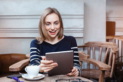 Young female student is chatting on digital tablet with friend while sitting in cafe, surprised attractive woman using Stock Images
