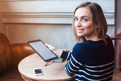 Young female student is enjoying free time,while is sitting with touch pad in coffee shop indoor. Beautiful woman is Stock Photography