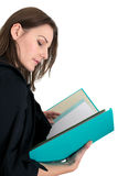 Young Female Student With A Folder/Binder. Reading from  it Stock Photos