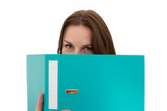 Young Female Student With A Folder/Binder. Young Female Student Hiding Behind A Folder/Binder Royalty Free Stock Photos