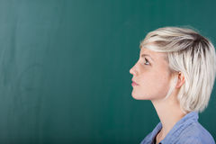 Young female student in front of the blackboard. A young female student standing in front of the blackboard and looking at something Stock Photography