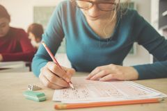 Young female student having examination in classroom royalty free stock images