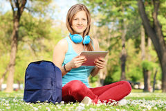Young female student with headphones and tablet in park Stock Photo