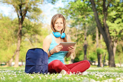Young female student with headphones and tablet sitting in park Stock Photography
