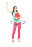 Young female student holding notebooks and playing with a hula-h Royalty Free Stock Images