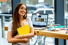 Young female student holding yellow book Royalty Free Stock Photo