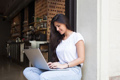 Young female student keyboarding on her laptop computer while sitting in restaurant in the fresh air in summer day Stock Photo