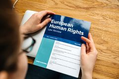Young female student lawyer reading European human Rights Law bo. PARIS, FRANCE - APR 26, 2017: Young female student lawyer reading European human Rights Law royalty free stock photography