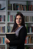 Young female student in library. Young beautiful female student studying in library Royalty Free Stock Photo