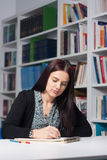 Young female student in library. Young beautiful female student studying in library Royalty Free Stock Photography