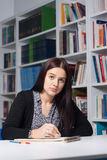 Young female student in library. Young beautiful female student studying in library Royalty Free Stock Images