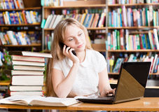 Young female student in library typing on laptop and talking on Royalty Free Stock Photos