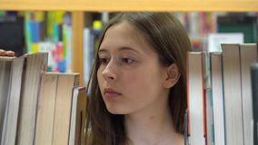 Young female student in the school library stock video