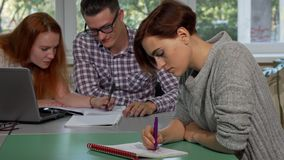 Young female student looking tired and confused while writing in her textbook stock photos
