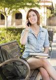 Young Female Student Outside Using Cell Phone Sitting on Bench. Smiling Young Pretty Female Student Outside on Cell Phone with Backpack and Books Sitting on Stock Photos