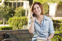 Young Female Student Outside Using Cell Phone Sitting on Bench. Smiling Young Pretty Female Student Outside on Cell Phone with Backpack and Books Sitting on Stock Images