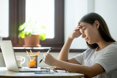 Young female student preparing exams on laptop at home. Lack of energy, boredom at work. Attractive millennial women studying on laptop and preparing graduating Stock Images