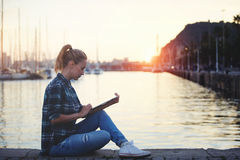 Young female student reading electronic book on digital tablet while sitting near sea port in summer evening, Stock Photo