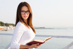 Young female student  in reading glasses with the book. Young female student  in reading glasses Royalty Free Stock Images