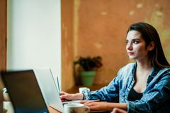 Young female student sits near the window with laptop and look through the window. stock image