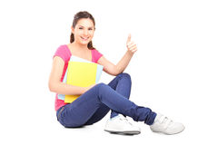 Young female student sitting on floor and giving thumb up Stock Photo