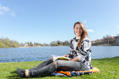 Young female student sitting in a park and reading a book Stock Photography