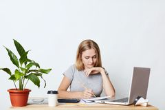 Young female student studying math, preparing report, making notes from laptop, writing in her copy book, isolated over white back. Ground. Business lady being Stock Photography