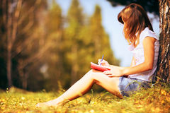Young female student studying outdoors in the autumn. Stock Image