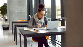 Young female student taking notes for her study. Young afro american woman sitting at table with books and laptop for finding information. Young student taking Royalty Free Stock Image