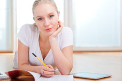 Young female student taking notes while studying Stock Images