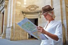 Young female student with trendy look examines atlas during traveling abroad in summer vacation stock photo
