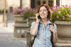 Young Female Student Walking Outside Using Cell Phone Stock Image