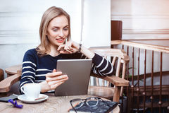 Young female student is watching movie on digital tablet while sitting in cafe, beautiful woman using laptop com Royalty Free Stock Image