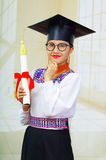 Young female student wearing traditional blouse, glasses and graduation hat, holding rolled up diploma, smiling proudly Stock Image