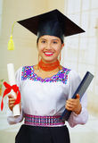 Young female student wearing traditional blouse with graduation hat, holding black diploma booklet and formal paper roll Royalty Free Stock Photos