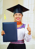 Young female student wearing traditional blouse and graduation hat, holding black diploma booklet, giving thumb up Royalty Free Stock Photography