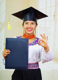 Young female student wearing traditional blouse and graduation hat, holding black diploma booklet, making positive Stock Images