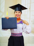 Young female student wearing traditional blouse and graduation hat, holding black diploma booklet while pointing at it Stock Photos