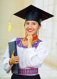 Young female student wearing traditional blouse and graduation hat, holding black diploma booklet while touching chin Royalty Free Stock Photography
