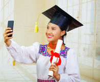 Young female student wearing traditional blouse with graduation hat, holding formal paper diploma roll while taking Royalty Free Stock Photos