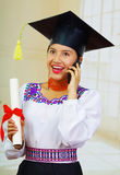 Young female student wearing traditional blouse with graduation hat, holding formal paper diploma roll while talking on Stock Photos