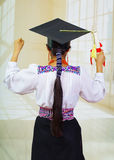 Young female student wearing traditional blouse and graduation hat, holding rolled up diploma, back facing camera Royalty Free Stock Photo