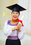 Young female student wearing traditional blouse and graduation hat, holding rolled up diploma, smiling proudly for Stock Photos