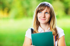 Young female student with workbook standing on green blurred grass background Stock Photography