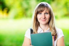 Young female student with workbook standing on green blurred grass background Royalty Free Stock Images