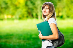 Young female student with workbook standing on green blurred grass background Stock Image