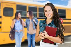 Young Female Students with Books Near School Bus. Young Teenaged Female Students Carrying Her Books Near a School Bus stock photos